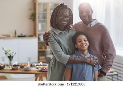 Portrait der glücklichen afroamerikanischen Familie, die die Kamera anschauen, während sie sich im Inneren in gemütlicher Inneneinrichtung mit Esstisch im Hintergrund, Kopienraum