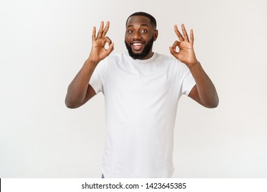 Portrait of happy african-american man showing ok sign and smiling, over white background.