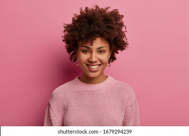 Portrait of happy Afro American woman has curly hairstyle, smiles and pleased expression, wears casual pink jumper in one tone with background, expresses happiness, glad to meet with close friend