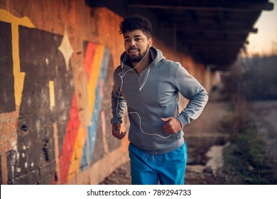 Portrait of happy afro-american attractive active runner man jogging outside on abandon place with earphones.