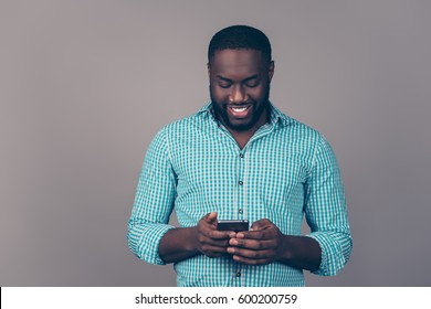 Portrait of happy afroamerican  bearded  man using smartphone and read sms
