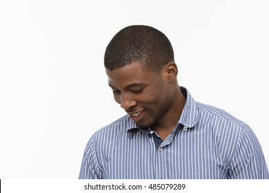 Portrait of happy Afro-American man looking down and smiling while posing isolated on white background in studio. Emotions concept.