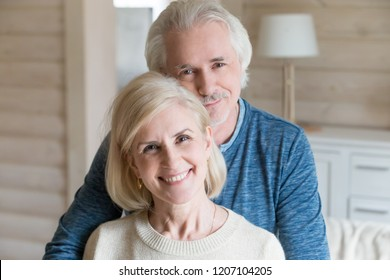Portrait of happy aged couple hugging posing for family picture at home, caring senior husband embrace wife from behind shooting together, loving elderly spouses looking at camera smiling for photo