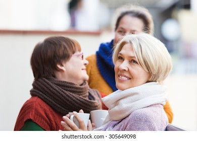 Portrait of happy aged female friends drinking coffee at patio. Focus on blonde