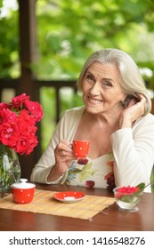 Portrait of a happy aged woman drinking coffee