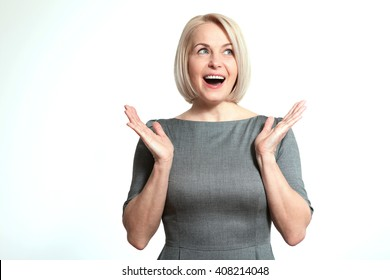 Portrait of happy aged woman. Surprised happy woman looking sideways in excitement. Isolated over white background