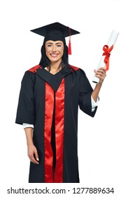 Portrait of happy alumni of university on white background. Young lady in black and red academical dress and square academic cap posing at camera. Girl holding diploma and celebrating graduation.