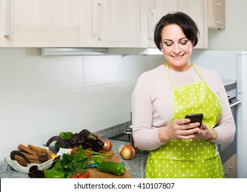 Portrait of happy american brunette housewife in apron receiving sms with recipe