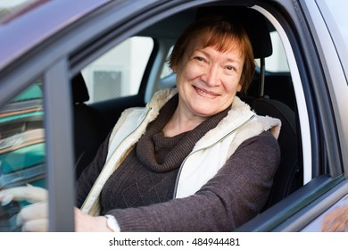 Portrait of happy american female senior driver smiling in car