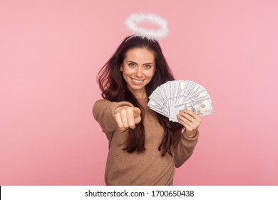 Portrait of happy angelic young woman with halo above head holding dollar banknotes and pointing to camera, choosing lottery winner, encouraging to earn big money. indoor studio shot, pink background