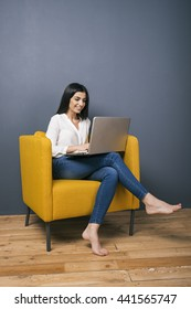 Portrait of happy Armenian woman on yellow arm-chair working on laptop.Copy space