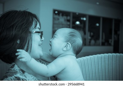 Portrait of happy asian baby with mom on weave bamboo chair, focus on baby