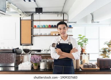 Portrait of happy Asian barista man with coffee tamper in his hand, smiling and looking at camera in the coffee shop