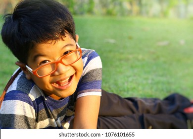 Portrait of happy asian boy sit on the green yard. Cute boy wear eye glasses is smiling, laughing at outdoor in warm sunlight