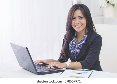 portrait of happy asian business woman using laptop computer while working