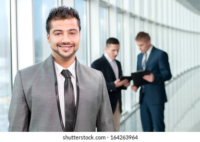 Portrait of a happy asian businessman in a modern office on a background of colleagues