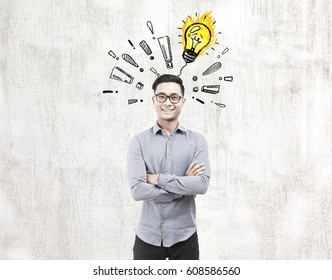 Portrait of a happy Asian businessman standing near a concrete wall with a ligth bulb surrounded by exclamation marks on it.