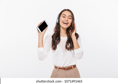 Portrait of a happy asian businesswoman listening to music with headphones and holding blank screen mobile phone isolated over white background