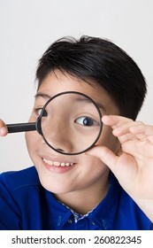 portrait of happy asian child looking through a magnifying glass on gray background
