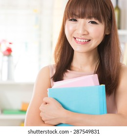 Portrait of happy Asian college girl hands holding books and smiling. Young woman at school library.