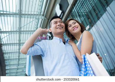 Portrait of happy Asian couple with shopping bags