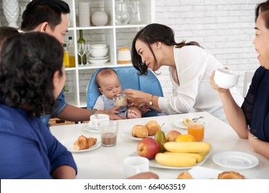 Portrait of happy Asian family at breakfast, mother feeding baby boy at dining table and smiling