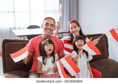 portrait of happy asian family celebrating indonesian independence day at home wearing red and white with indonesia flag