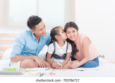Portrait of happy Asian family. Father, daughter kissing mother in bedroom.