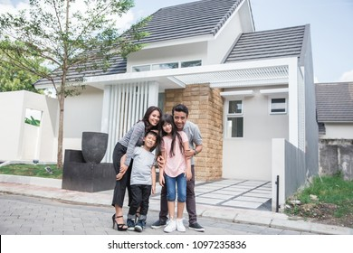 portrait of happy asian family in front of their new house