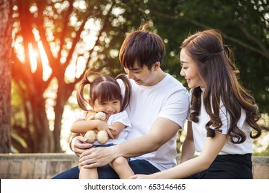 Portrait Of Happy Asian Family In Garden