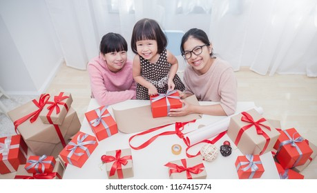 Portrait of happy Asian family little girls help her mother wrapping gift box, celebration holiday christmas mother's day. Modern lifestyle people love fun together childhood concept banner