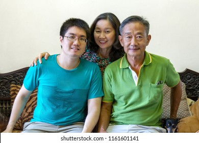portrait of happy asian family sitting on couch