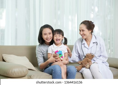 Portrait of happy Asian family sitting together with female doctor on sofa and laughing
