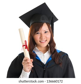Portrait of happy Asian female student in graduate gown holding graduation diploma isolated on white background