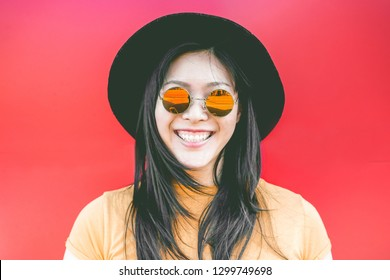 Portrait of happy asian girl smiling with vintage sunglasses - Young chinese woman having fun posing in front of the camera - Fashion, trendy and millennial generation concept - Focus on  glasses