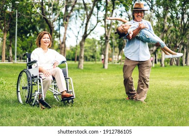 Portrait of happy asian grandfather with grandmother and asian little cute girl enjoy relax in summer park.Young girl with their laughing grandparents smiling together.Family and togetherness