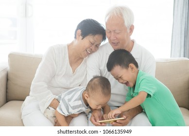 Portrait of happy Asian grandparents and grandchildren using smart phone at home, family indoor lifestyle.