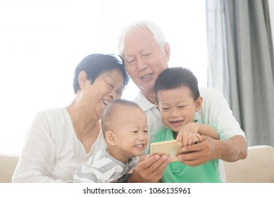 Portrait of happy Asian grandparents and grandchildren selfie using smart phone at home, family indoor lifestyle.