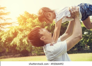 Portrait of happy asian little girl with her father in the garden