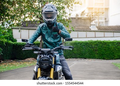 Portrait of happy asian man in green leather jacket riding on motorbike in city street and showing thumb up