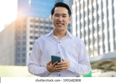 Portrait happy asian man holding smart phone and looking at camera with smile face in cityscape background Handsome confident young guy standing and smiling in white shirt Business man get satisfied