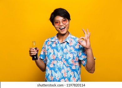 Portrait of a happy asian man isolated over yellow background, holding bottle with fizzy drink