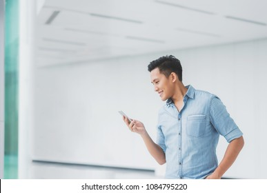 Portrait of Happy Asian man looking on a smartphone in building with copyspace