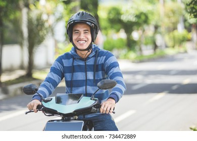 portrait of happy asian man riding on motorbike in city street
