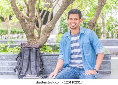 Portrait of happy Asian man, Smiling handsome guy in denim jacket and jeans sitting relaxed in city park
