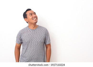 Portrait of happy Asian man standing while looking up. Isolated on white background with copyspace