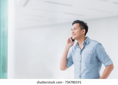 Portrait of Happy Asian man talking on a smartphone in building with copyspace