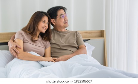Portrait of happy Asian middle-aged couple sitting on a bed, husband put his hand over the shoulder of the wife smiling to a camera in a bedroom. Warmth family concept.