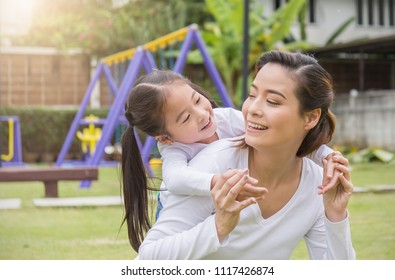 Portrait of happy asian mother and daughter. Asian woman and little toddler girl cuddling and hugging in the playground park. Happy family green spring or summer mother's day together concept