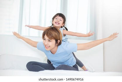 Portrait of happy asian mother and daughter laughing flying in bed. Mommy and little girl spending time at home. Fun love family woman lifestyle together mother's day background concept banner